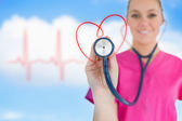 Happy nurse holding up stethoscope to heart design — Stock Photo