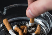Hand putting out a cigarette in ashtray — Stock Photo