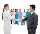 Business shaking hands with medical staff in background — Stok fotoğraf
