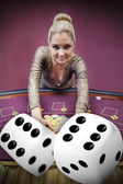 Blonde woman grabbing chips with digital dice — Stock Photo