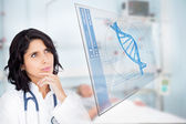Doctor studying virtual screen showing DNA helix — Stock Photo