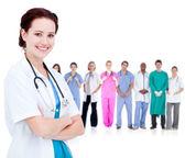 Doctor sonriente frente a un equipo de médicos parados juntos — Foto de Stock