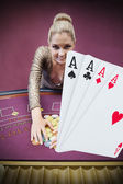 Blonde woman grabbing chips with digital hand of four aces — Stock Photo