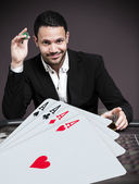 Handsome gambler betting on four aces at poker table — Stock Photo