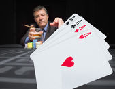 Gambler at the poker table with digital hand in foreground — Stock Photo