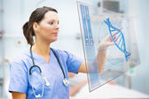 Nurse touching screen displaying blue DNA helix — Foto Stock