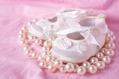 White baby booties with string of pearls — Stock Photo