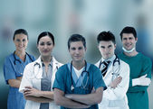 Smiling hospital workers standing arms crossed in line — Stock Photo