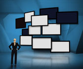 Group of blank screens on blue background with businesswoman looking up — Stock Photo