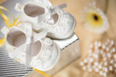Baby booties on gift box — Stock Photo