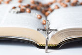 Cross of rosary beads resting against bible — Stok fotoğraf