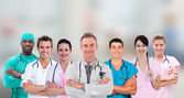 Medical team standing arms crossed in line — Stock Photo