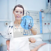 Nurse touching screen displaying blue human form — Foto Stock