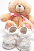 Teddy bear for a girl with white baby booties — Stock Photo