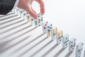 Hand placing domino into line of dominoes — Stock Photo