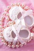 Overhead of white baby booties with string of pearls — Stock Photo