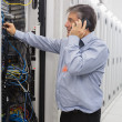 Male technician phoning while repairing a server - Stock Photo