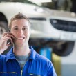 Car mechanic using mobile phone — Stock Photo
