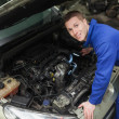 Happy mechanic examining car engine — Stock Photo #24091601