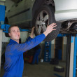 Car on hydraulic lift as mechanic examining tire — Stock Photo #24091609