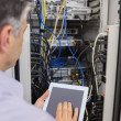 Technician controlling the server with a digital tablet - Stock Photo
