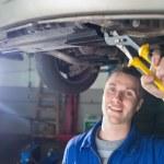 Happy mechanic repairing car with pliers — Stock Photo