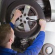 Mechanic fixing car wheel - Stock Photo