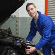 Happy mechanic with battery by car — Stock Photo #24091685