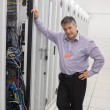 Stock Photo: Mstanding next to server tower