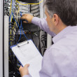 Stock Photo: Electricidoing server maintenance with clipboard