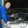 Mechanic by car holding digital tablet — Stock Photo #24091921