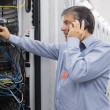 Technician phoning while repairing the server - Stock Photo