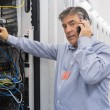 Stock Photo: Technician working on server and phoning