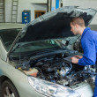 Stock Photo: Mechanic analyzing car engine