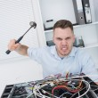 Portrait of frustrated mhitting cpu with hammer — Stock Photo #24092123