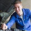 Foto de Stock  : Male mechanic working on automobile engine