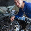 Mechanic working under bonnet of car - Stock Photo