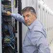 Technician looking up from adjusting server wires — Stock Photo