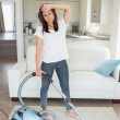 Tired woman hoovering the living room — Stock Photo #24092321