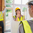 Woman and architect talking while man is measuring wooden frame — Stock Photo