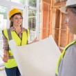 Womand architect discussing blueprint — Stock Photo #24092603