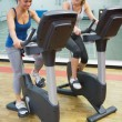 Two laughing women on exercise bikes — Stock Photo
