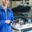 Happy mechanic using tablet computer — Stock Photo