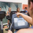 Instructor motivates happy at spinning class — Stock fotografie