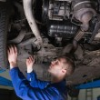 Foto Stock: Mechanic under car in garage