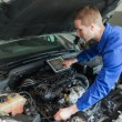 Mechanic with digital tablet repairing car engine — Stock Photo