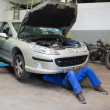 Stock Photo: Male mechanic working under car