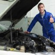 Mechanic by car gesturing thumbs up — Stock Photo #24093509
