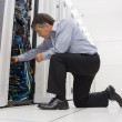 Technician kneeling and repairing a server with his hands — Stock Photo #24093599