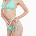 Woman in bikini measuring waist — Stock Photo #24093669